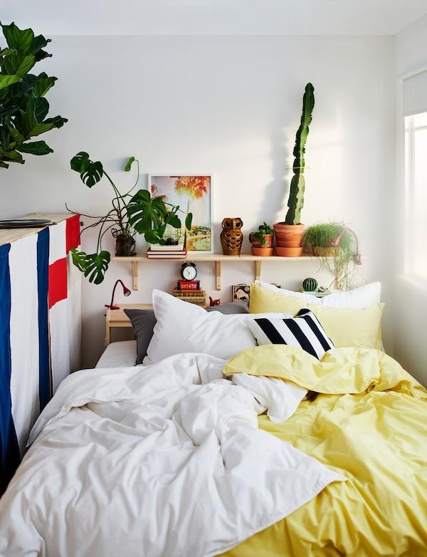 Schlafzimmer mit gelber Bettwäsche und vielen Pflanzen auf einem Holzbrett