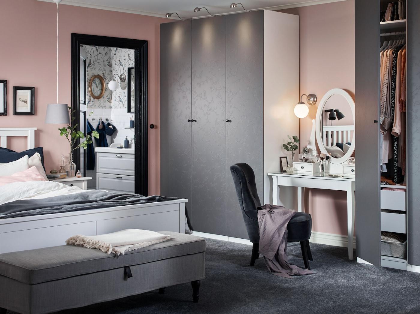 Schlafzimmer mit rosa Wänden, grauen Schränken, weißem Bett & Schminktisch mit grauem Sessel.