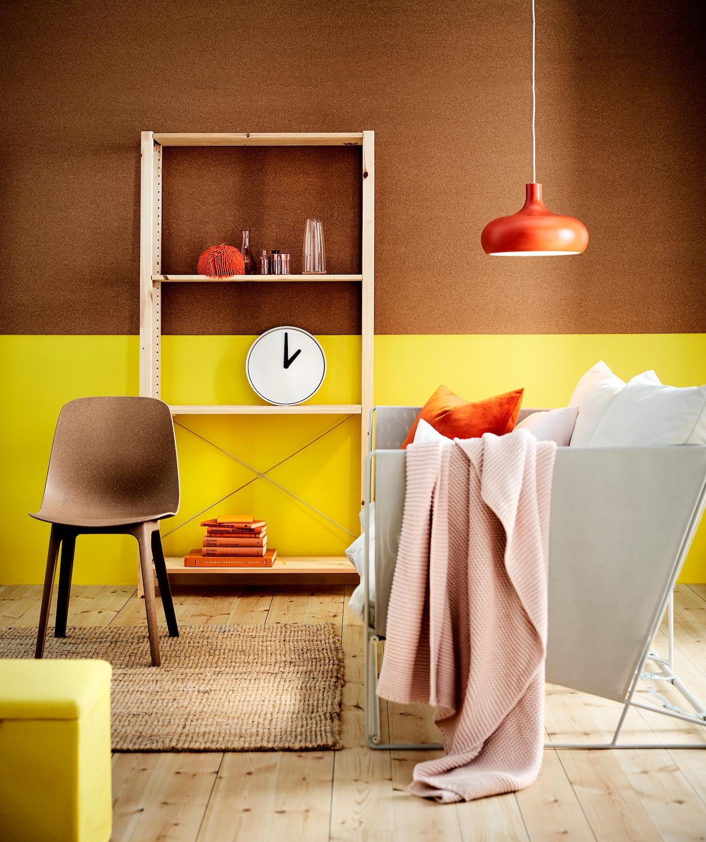 Schlichte Wohnzimmerecke mit weißem Gartensofa, roten Accessoires & gelb-braun gestrichenen Wänden