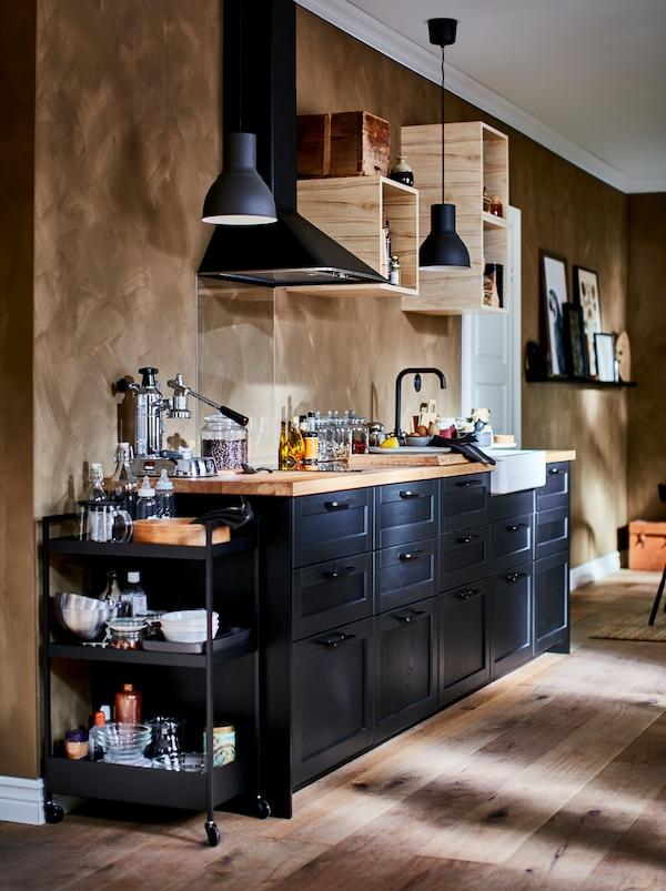 Schön ausgestattete Küchenzeile mit kleinen, offenen Wandschränken, einer Dunstabzugshaube, einem schwarzen Servierwagen und LERHYTTAN Schubladenfronten.