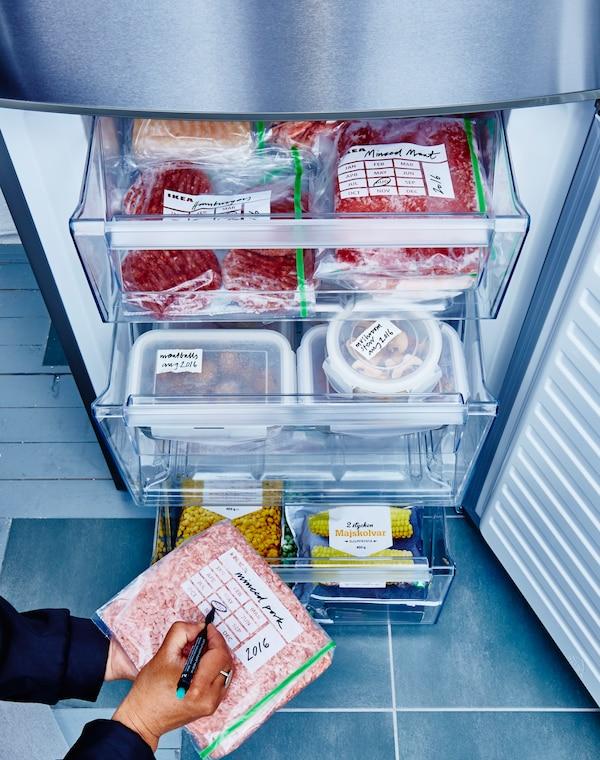 Schubladen eines Gefrierschranks, darin Lebensmittel in beschrifteten ISTAD Kunststoffbeuteln in Grün