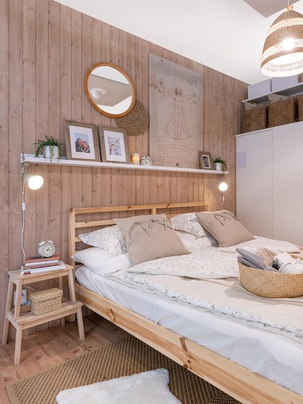 Schůdky BEKVÄM, polička nad postelí na které jsou osobní fotografie a doplňky.