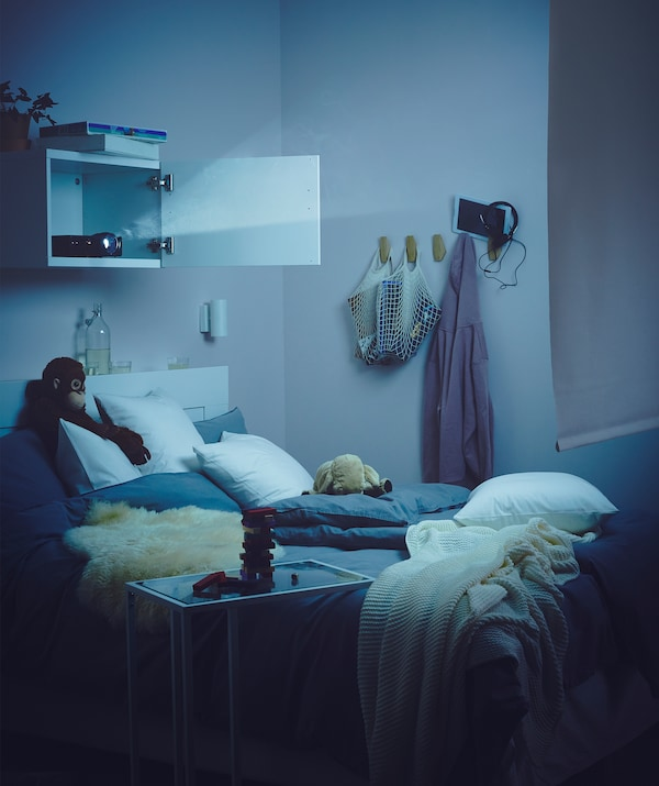 Schwach erhelltes Schlafzimmer, in dem u. a. ein BESTÅ Regal mit Tür zu sehen ist, in dem ein Beamer steht.