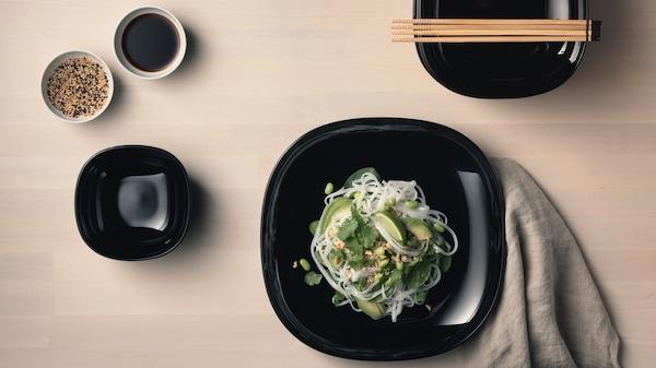 Schwarze BACKIG Teller mit Asiatischem Essen darauf