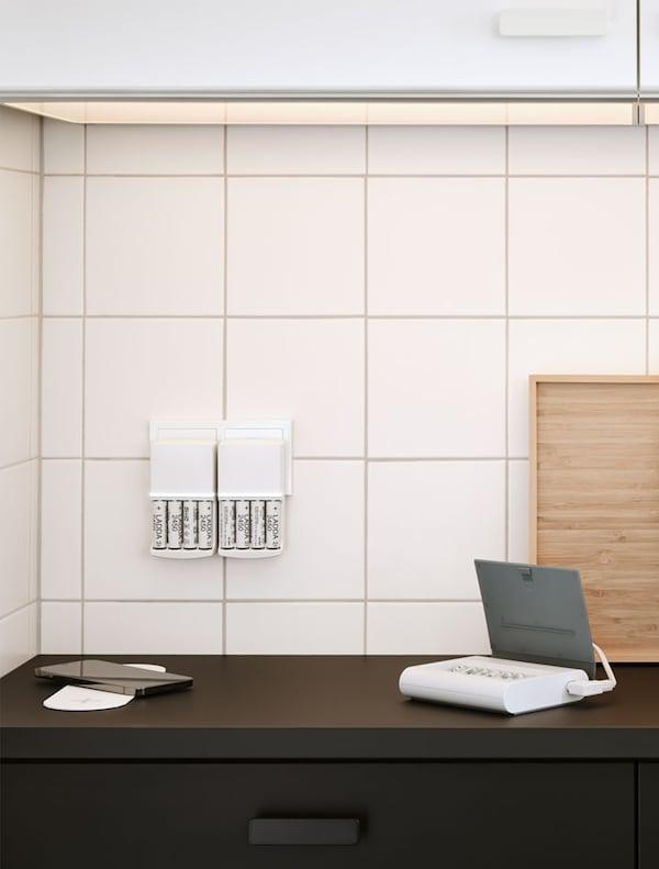 Schwarze Küche mit weißen Wandkacheln. Auf der Arbeitsplatte liegt ein Ladegerät für ein Smartphone, ein Akku und eine Batterieladestation an der Wand.