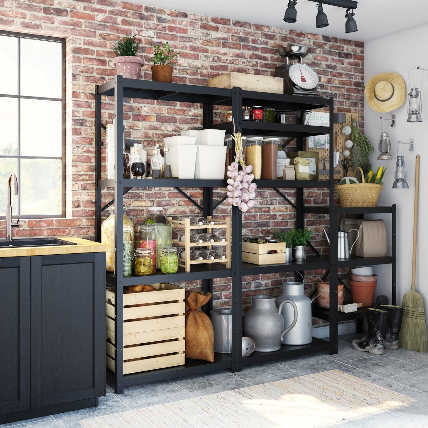 Schwarzes Vorratsregal in einem Kellerraum mit Holzkisten, grauen Kannen, Lebensmitteln, Körben & Besen.