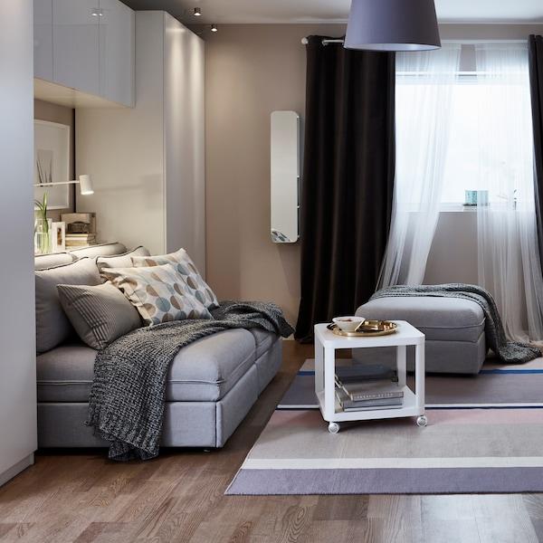 Ściana w pokoju dziennym z szafą i szafkami ściennymi z białymi frontami. Szara sofa rozkładana z biłaym stolikiem na kółkach.