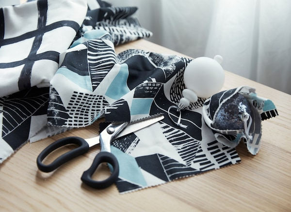 Scissors and graphic patterned fabric on a table, used to prepare small snippets of fabric to wrap holiday decorations.