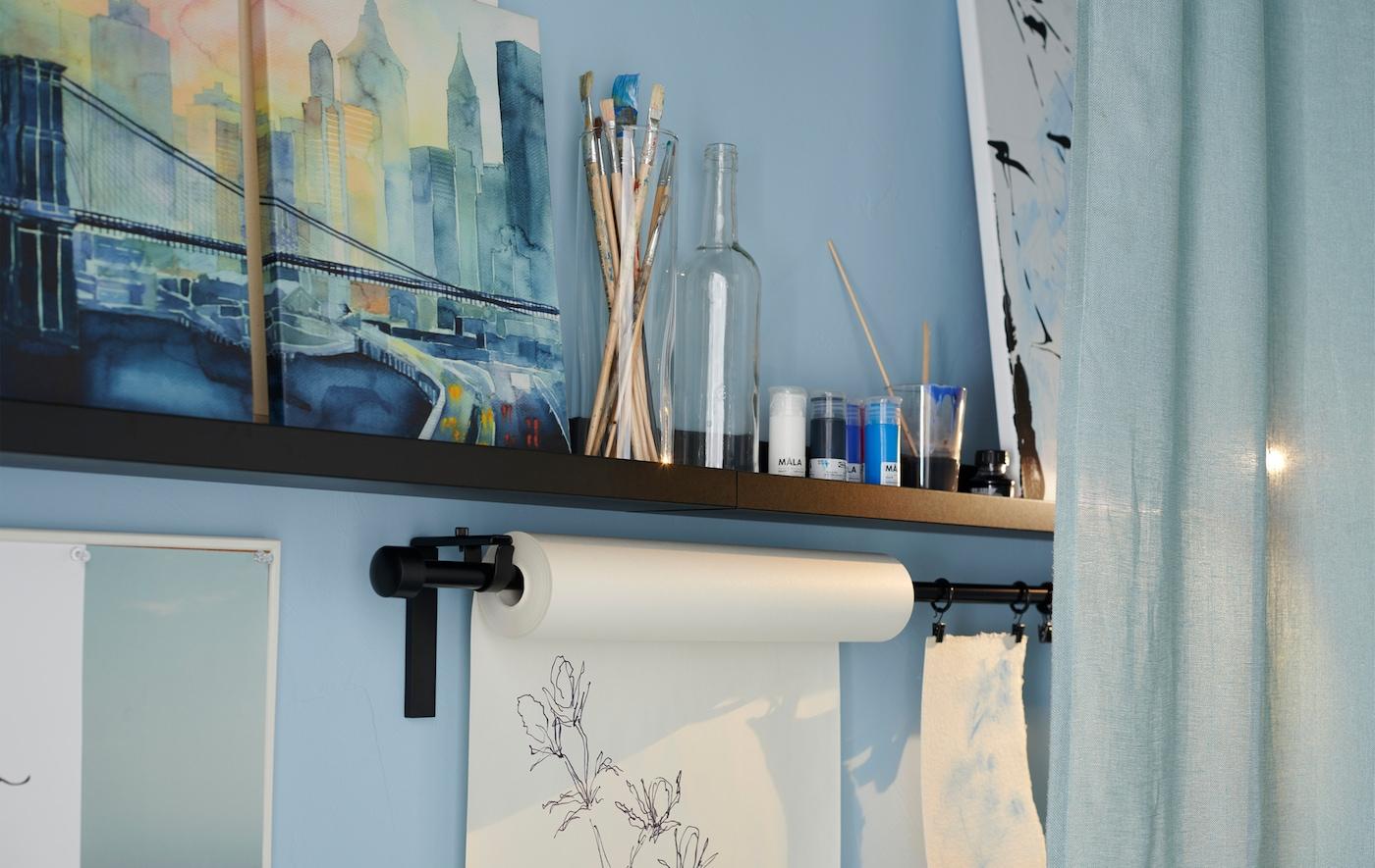 Scopri come realizzare su una parete una postazione creativa permanente che ti consente di liberare la vena artistica in qualsiasi momento. Per esporre le tue opere, prova la mensola per quadri nera MOSSLANDA di IKEA.