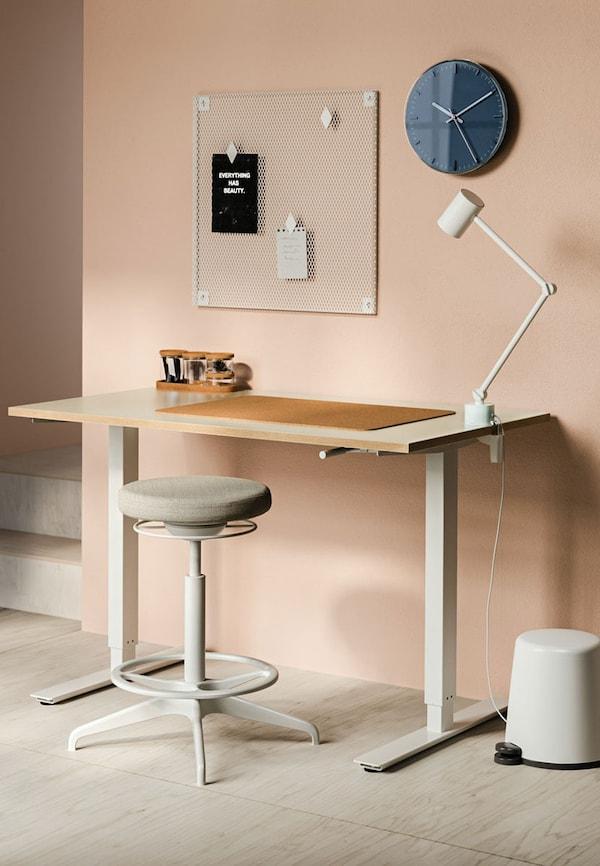 Scrivania e sgabello con lampada da tavolo appoggiata. Orologio appeso.