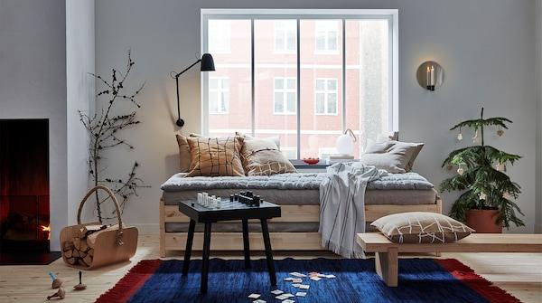 Se muestra un salón con artículos VÄRMER: cojines, banco de madera, tablero de ajedrez, alfombra, cesto, peonzas y candelabro de pared.