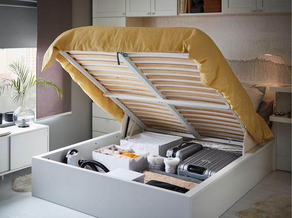 Se puede ver el espacio de almacenaje debajo de la cama blanca IKEA MALM, con colchas, almohadas y ropa de otra temporada.