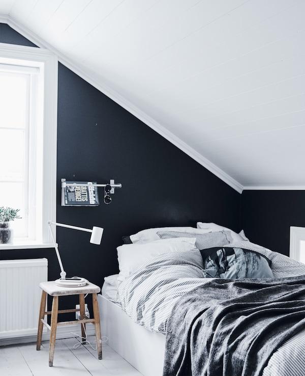 Se usa un estante de cocina con función de exposición en este dormitorio con paredes negras y suelo y pared blancas.