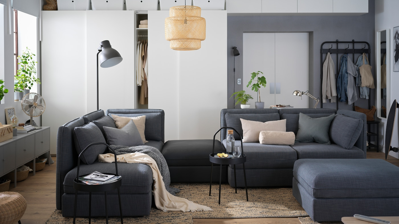 Seating and storage in a one-room city apartment, including a large VALLENTUNA modular sofa and PAX wardrobes.