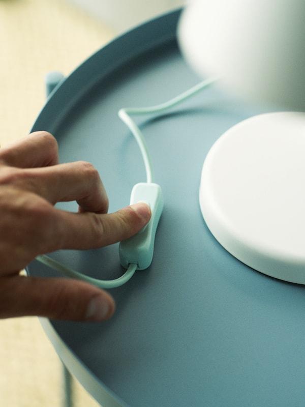 Sebelah tangan menekan suis lampu meja berwarna putih yang terletak di atas meja berwarna biru muda.