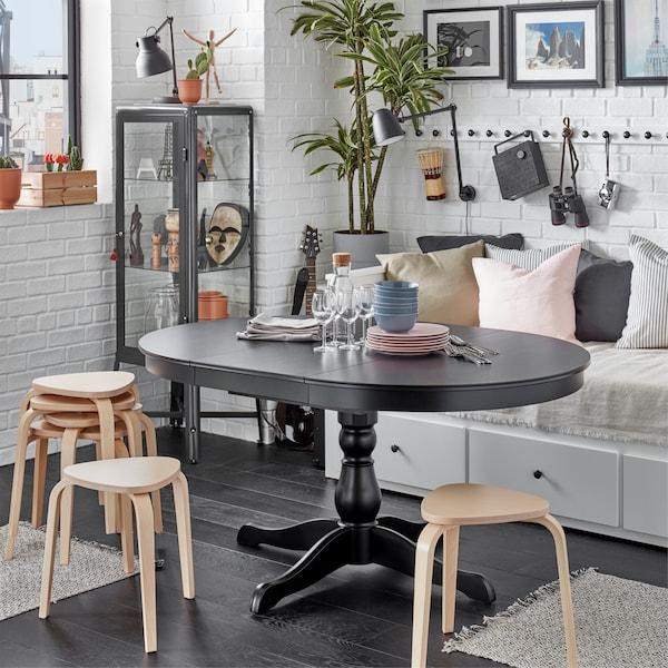 Sebuah meja boleh dipanjangkan INGATORP berwarna hitam dipanjangkan dan dikelilingi oleh beberapa bangku KYRRE yang menyediakan tempat duduk tambahan.