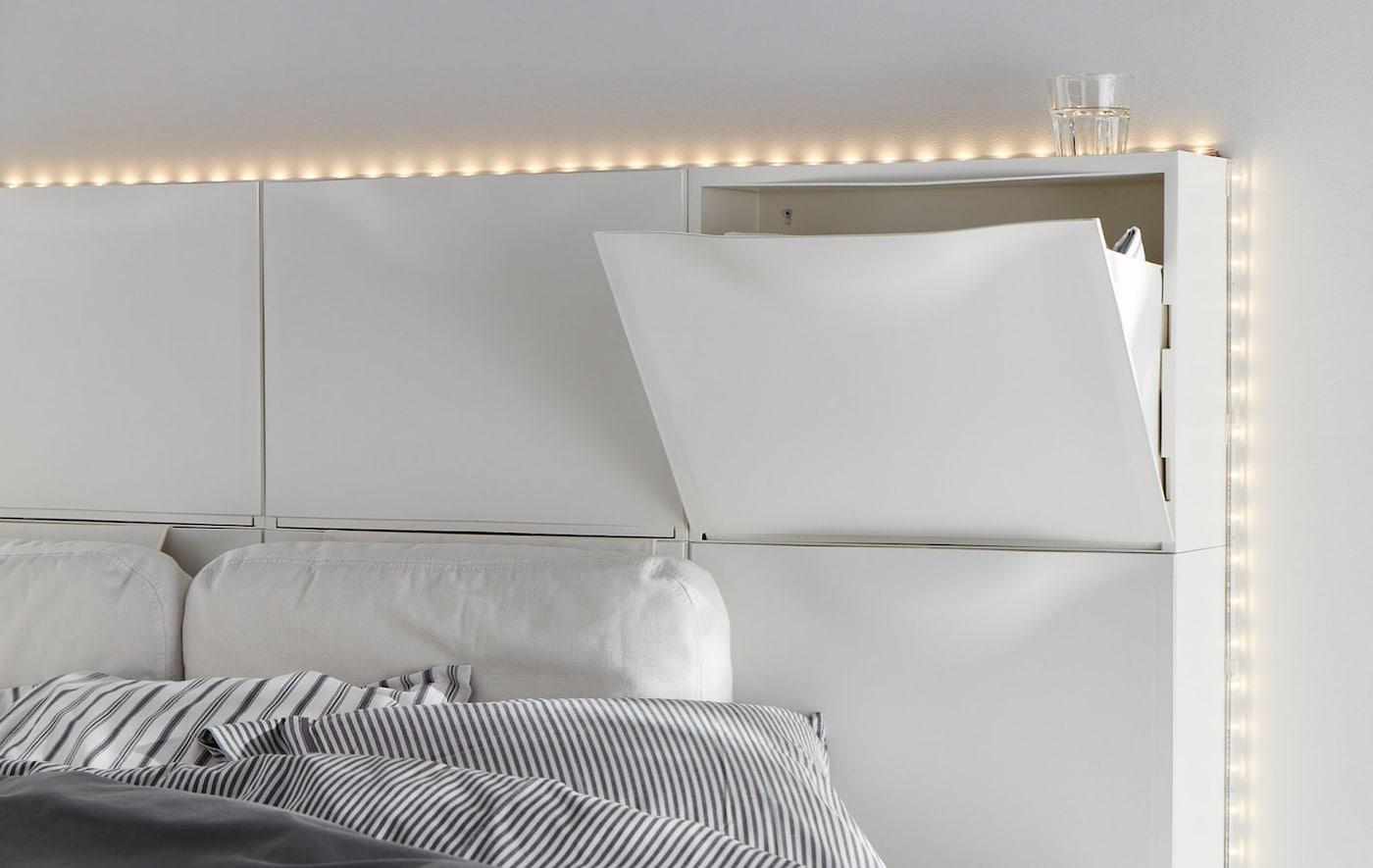 Sechs weiße IKEA TRONES Aufbewahrungen als Kopfteil für ein Bett.
