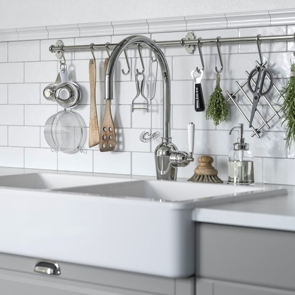 Secramiczny zlew kuchenny i srebrna bateria w kuchni z szarymi frontami.