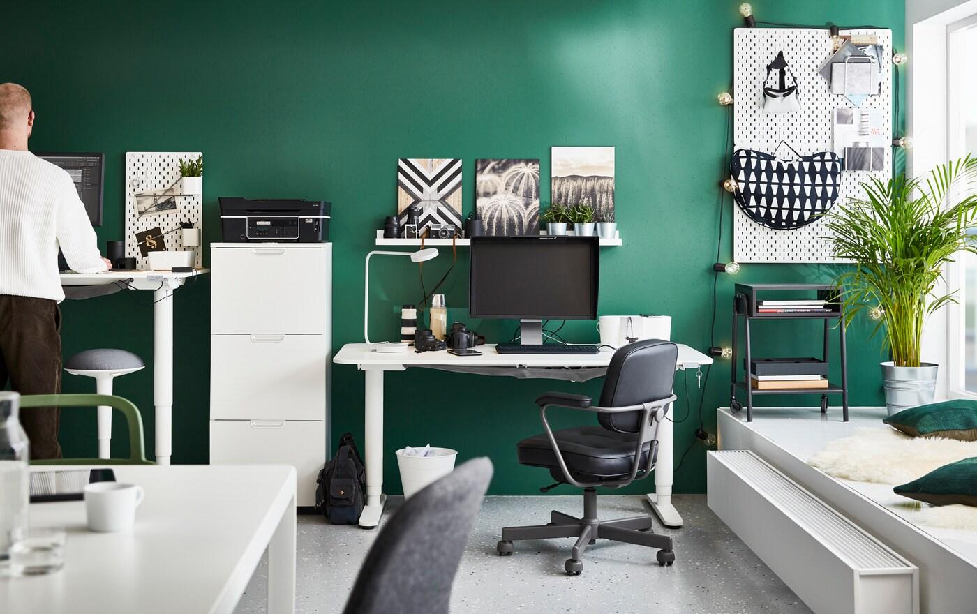 Secretárias sentado/em pé BEKANT, em branco, num espaço de escritório com paredes em verde, com cadeira giratória ALEFJÄLL, em preto, e banco de apoio de pé NILSERIK.