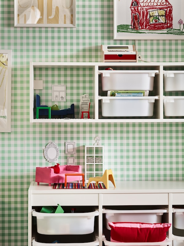 Section d'un mur à damiers vert et blanc avec un rangement TROFAST, fixé au mur et sur le plancher.