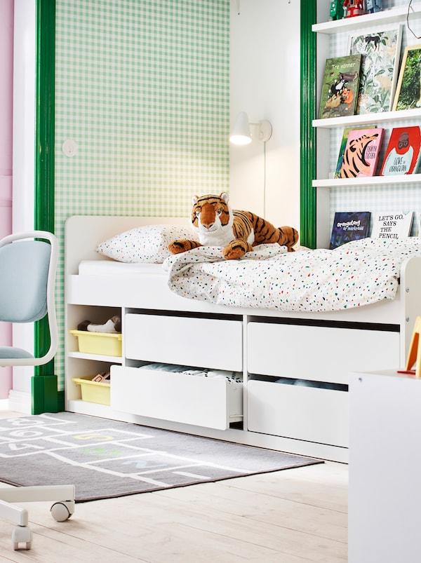 Section d'une chambre d'enfant en vert et blanc, avec des livres sur des cimaises, des jouets et un lit SLÄKT avec rangement sous le lit.