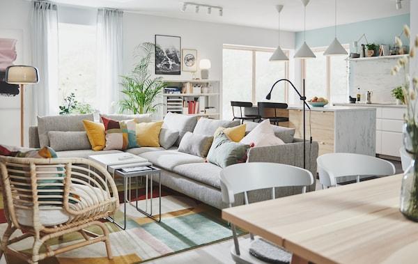 Section d'une grande pièce avec un coin-cuisine et un îlot de cuisine, près d'un coin-salon meublé d'un grand canapé d'angle.