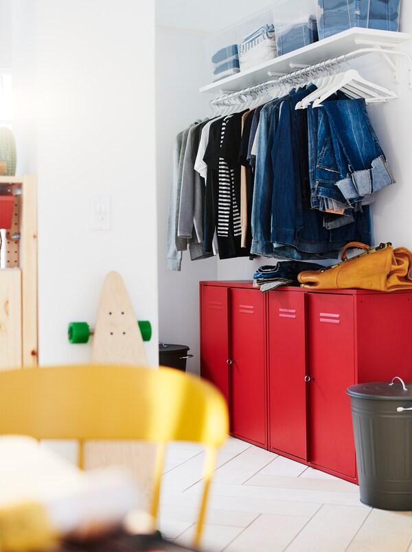 Section murale avec armoire-penderie et rangement de couloir combinés: armoires IVAR rouges sous une rangée de vêtements pendus sur des cintres sur une tringle.