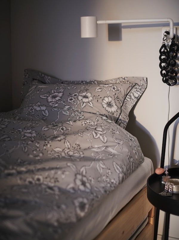 Section of a bed made with floral-patterned PRAKTBRÄCKA bed linen. A NYMÅNE wall lamp is poised for bedtime reading.