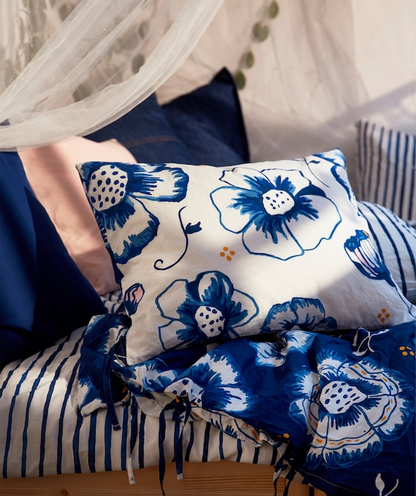Section of a bed with bedlinen, pillows and cushions in a blue-white mix of floral patterns, pinstripes and unicolour.