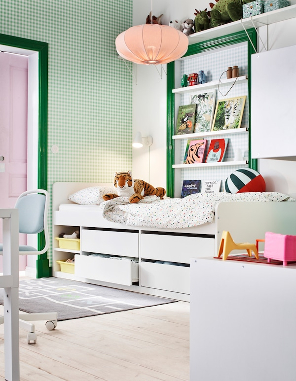 Section of a children's room in a green-and-white color scheme, with books, toys and a raised bed with under-bed storage.