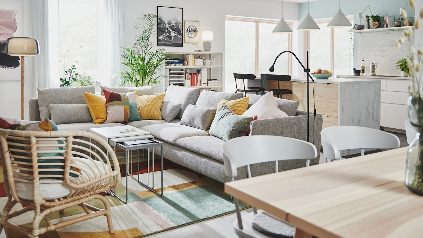 Section of a large room with kitchen area with kitchen island, next to a living-room area with large corner sofa.