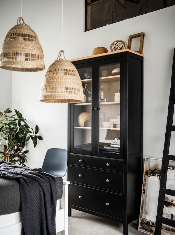 Section of a light bedroom with a tall, black HEMNES glass-door cabinet, TORARED pendant lamps, decorations and a plant.