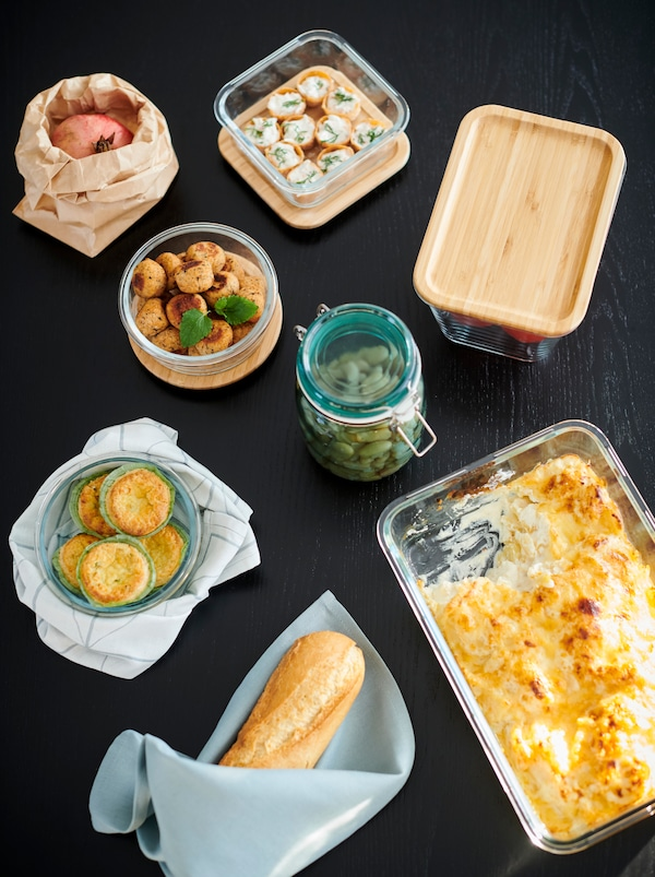 Section of a table with a mix of jars, an oven dish and IKEA 365+ food containers, all filled with different dishes.