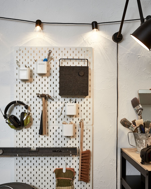 Section of a wall fitted with a pegboard holding tools, earphones and a bluetooth speaker; lighting chain and lamp.
