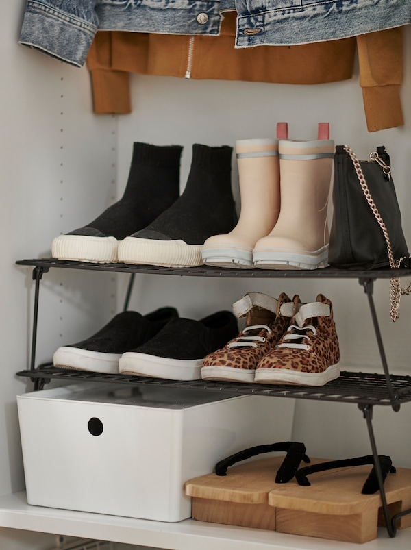 Section of a wardrobe cabinet in which a full GREJIG shoe rack stands amid other clothes and accessories.