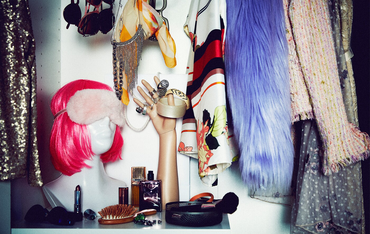Section of a wardrobe filled with flamboyant party clothing and accessories; bust with neon wig, mannequin hand with rings.