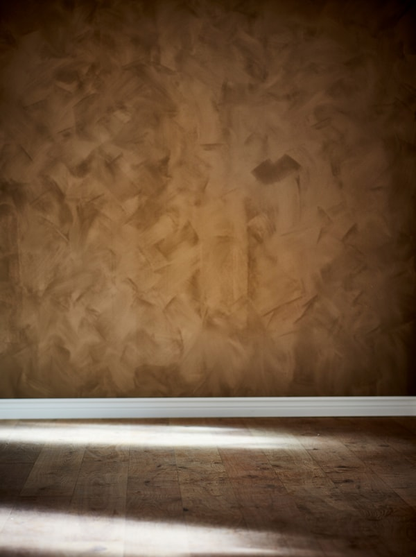 Section of an empty room with wooden floor and the wall painted in a rich, brown tone with a matte suede finish.