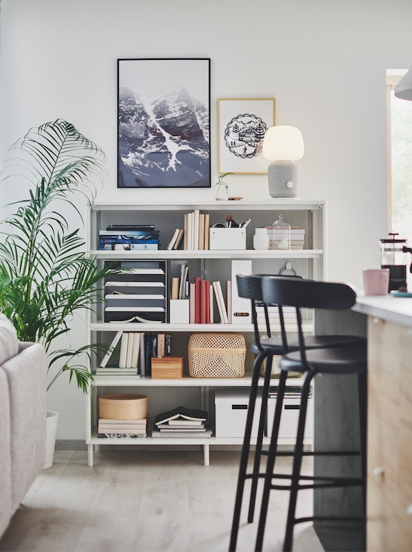 Section of an open floor-plan interior including a kitchen island, a living-room sofa, and a full BEKANT shelving unit.