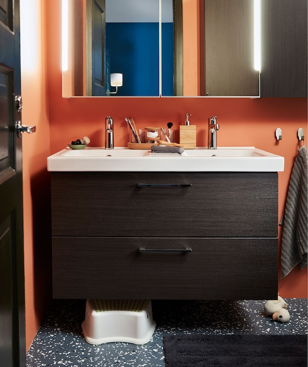 Section of bathroom with double washstand with drawers. Mirror-front cabinet above, children's stool and rubber duck below.