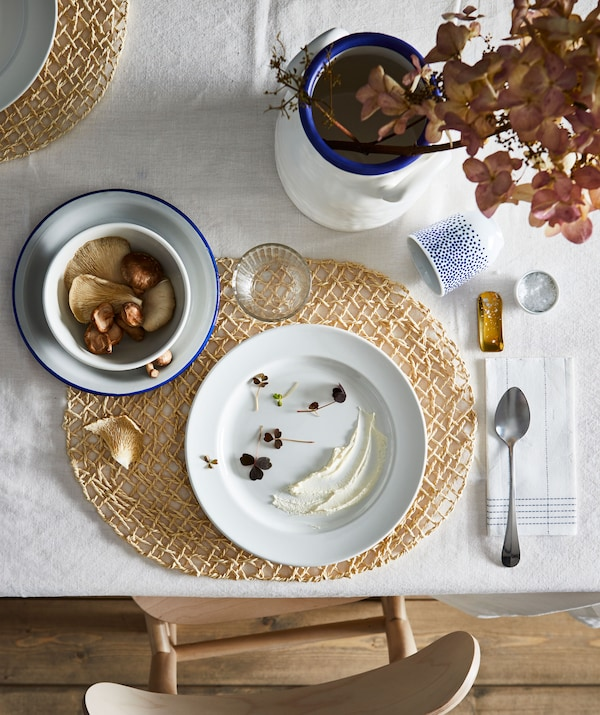 Section of dining table with an artful setting for one, including coordinated colours, shapes and decorations.