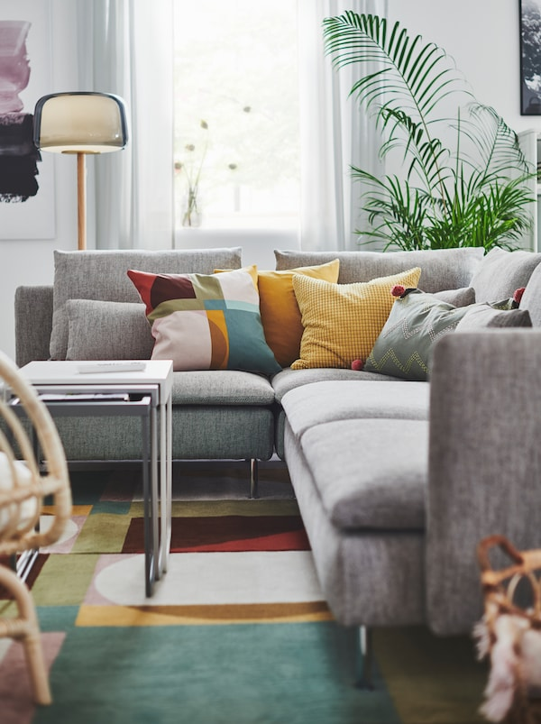 Section of living room with a gray SÖDERHAMN corner sofa, a host of colorful cushions on it and standing on a colorful rug.