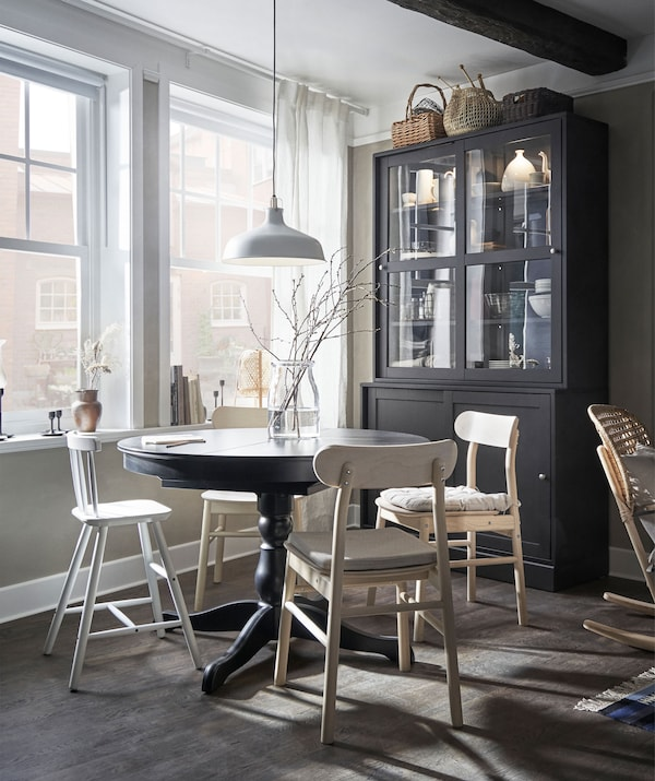 Section of living room with big windows. Dining table with seating for a small family, beside it a high, traditional cabinet.