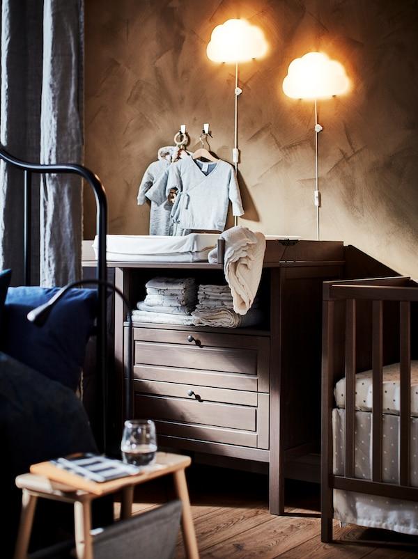 Secțiune a unei camere de zi ascunse pe jumătate în spatele unei perdele cu rol de compartimentare a încăperii, cu un pătuț pentru bebeluși și o masă de înfășat SUNDVIK.