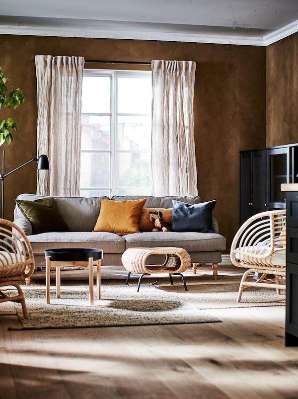 Secțiune a unei camere de zi zugrăvită și amenajată în nuanțe bogate și naturale: corpuri de depozitare, scaune, măsuță de cafea și un taburet cu spațiu de depozitare GAMLEHULT.
