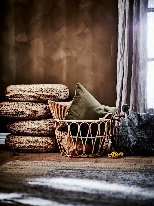 Secțiune a unui dormitor într-o nuanță de maro: perete maro, coșuri de ratan SNIDAD, taburete ALSEDA și covoare din materiale naturale.