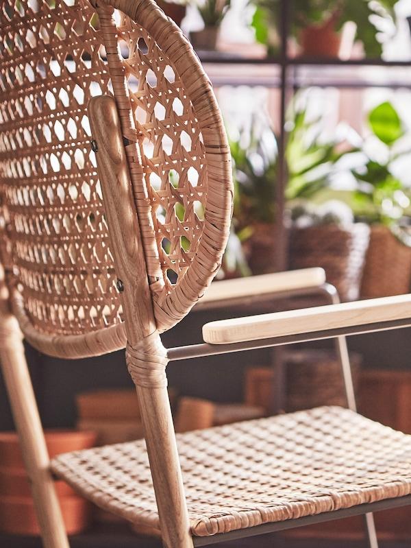 Sedia a dondolo GRÖNADAL di IKEA vicino a portavasi con piante.