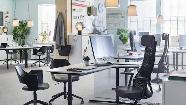 Sedie da ufficio regolabili JÄRVFJÄLLET, in nero, e scrivanie regolabili in altezza bianche, dal design lineare, in un ampio ambiente di lavoro open space.