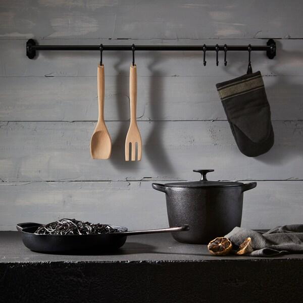 Šedo-černá  kuchyně, černé litinové hrnce, na desce stojí černý litinový hrnec a pánvička.