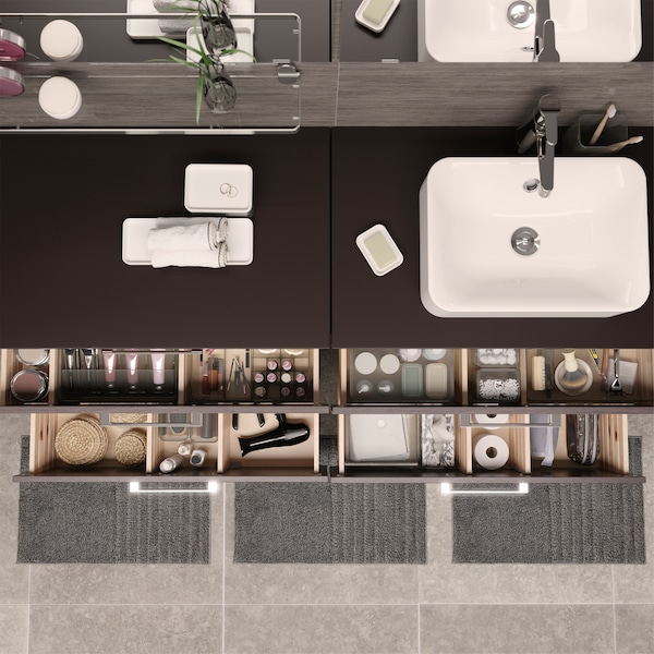 Seen from above are four open bathroom drawers where things are nicely organised in see-through boxes with compartments.