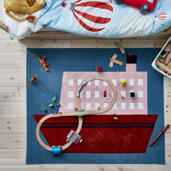 Seen from above is a blue, pink and red rug in a boat pattern, and lots of toys and a train set with rail are placed on it.